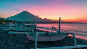 Zonsondergang die de Agung-vulkaan timelapse op de achtergrond van vissersboten op het strand van Djemeliuk in Amed overzien stock video