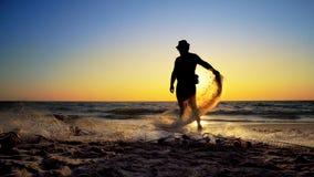 Zonsondergang die fishermans netto vangende vissen op oceaan trekken stock afbeeldingen