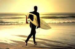 Zonsondergang die surfer loopt Stock Afbeelding