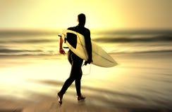 Zonsondergang die surfer loopt royalty-vrije stock foto