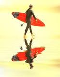 Zonsondergang die surfer loopt stock foto