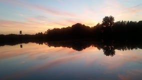 Zonsondergang die van het water wordt weerspiegeld Stock Foto's