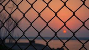 Zonsondergang door de omheining wordt gevangen die royalty-vrije stock afbeeldingen