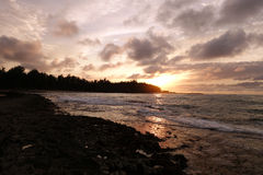 Zonsondergang door de wolken en het overdenken de golven aangezien zij br Royalty-vrije Stock Foto