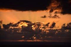 Zonsondergang door de wolken over de oceaan stock fotografie