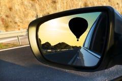 Zonsondergang in een auto wordt weerspiegeld die stock afbeelding