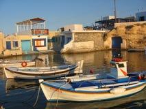 Zonsondergang in een kleine vissershaven en zijn boten van Milos-eiland in Griekenland Stock Foto's