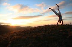 Zonsondergang en acrobatisch meisje Stock Foto's