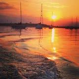 Zonsondergang en boten stock afbeelding