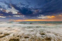 Zonsondergang en de golven die op de rotsachtige kust omwikkelen stock fotografie