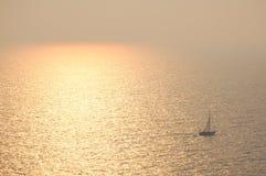 Zonsondergang en een boot Stock Afbeelding