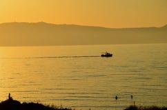 Zonsondergang en een boot Stock Fotografie