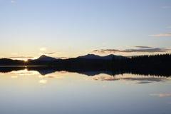 Zonsondergang en een kalm meer en bergen op achtergrond Royalty-vrije Stock Foto