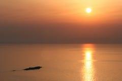 Zonsondergang en een rots stock afbeelding