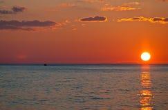 Zonsondergang en eenzame boot Royalty-vrije Stock Foto's