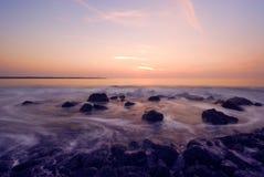 Zonsondergang en golven stock foto's