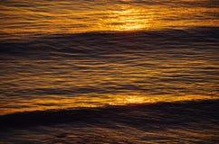 Zonsondergang en golven stock fotografie