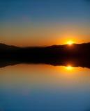 Zonsondergang en het golven vijverbezinning. stock foto's