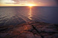 Zonsondergang en licht van de zon op het overzees en de rots Stock Foto