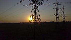 Zonsondergang en machtspyloon Met hoog voltage stock footage