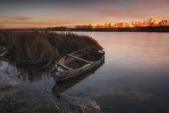 Zonsondergang en oude boot royalty-vrije stock foto