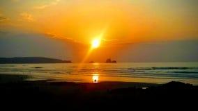 Zonsondergang en paar in de afstand die dichtbij de kust kijken royalty-vrije stock afbeeldingen