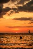 Zonsondergang en silhouetten op een tropische oceaan Stock Afbeelding