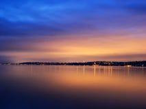 Zonsondergang en stedelijke die lichten in water wordt weerspiegeld Stock Afbeelding