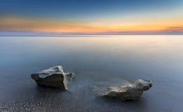 Zonsondergang en tworocks in het zijdeachtige water Stock Fotografie
