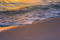 Zonsondergang, golf en zand stock foto's