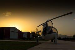 Zonsondergang, helikopter op land Stock Fotografie