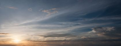 Zonsondergang in hemel: de zonreeksen achter de wolken, witte die wolken aan de donkere hemel, oranje glans zijn gescheiden Royalty-vrije Stock Afbeeldingen