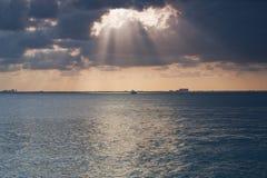 Zonsondergang het Doordringen door de Wolken over de Oceaan Stock Afbeelding