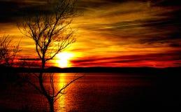 Zonsondergang in het meer en de bergen stock foto's