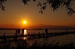 Zonsondergang in het meer met mensen Stock Foto's