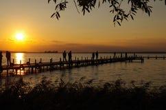 Zonsondergang in het meer met mensen Royalty-vrije Stock Fotografie
