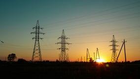 Zonsondergang in het platteland naast de weg en het overgaan van auto's amid machtslijnen met hoog voltage Tijdoverlappingen stock video