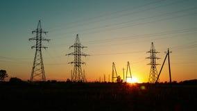Zonsondergang in het platteland tegen de achtergrond van machtslijnen met hoog voltage Tijdoverlappingen stock videobeelden