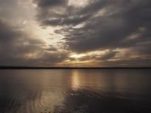 Zonsondergang in meer wordt weerspiegeld dat Royalty-vrije Stock Afbeeldingen