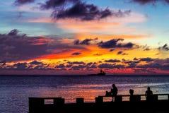 Zonsondergang, mensensilhouetten en het schip stock foto's