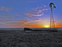 Zonsondergang met bestelwagen en windmolen op vlaktes Stock Foto