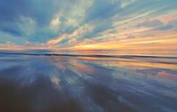 Zonsondergang met bezinning over zand met lichte gezoemblura Royalty-vrije Stock Afbeeldingen