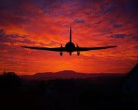 Zonsondergang met een vliegtuigsilhouet Stock Fotografie