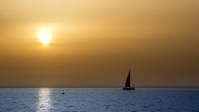 Zonsondergang met een zeil royalty-vrije stock afbeeldingen