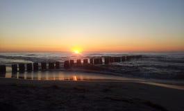Zonsondergang met golfbreker door de Oostzee Stock Foto