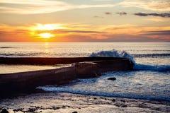 Zonsondergang met golven en wavesbreaker Royalty-vrije Stock Foto's