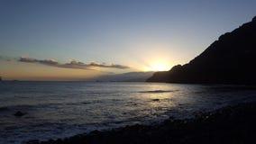 Zonsondergang met het overzees en de bergen royalty-vrije stock foto