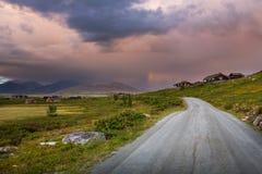 Zonsondergang met hutten en weg in Noorwegen stock foto