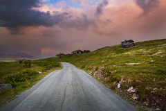 Zonsondergang met hutten en weg in Noorwegen royalty-vrije stock foto's