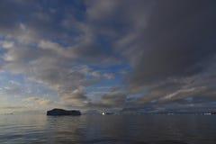 Zonsondergang met ijsbergen stock foto's